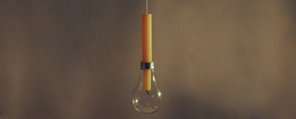 Photo of an orange candle inserted into a lightbulb.